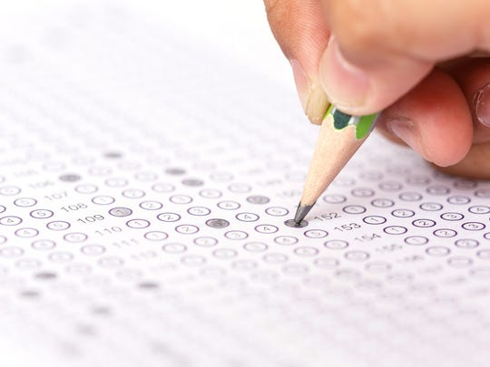 A student fills in a bubble answer sheet during a standardized