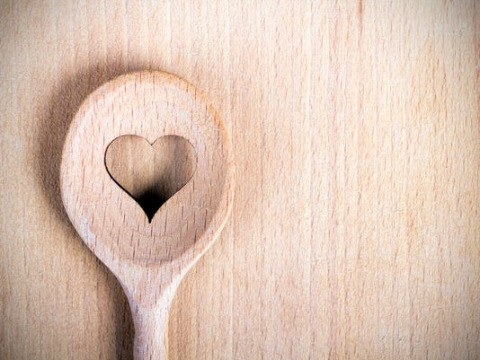 Heart hole spoon on the wooden pastry board