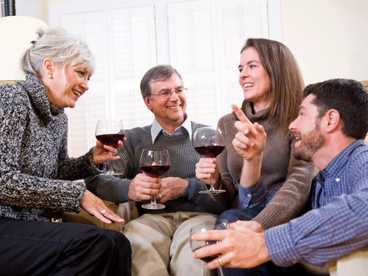 Senior couple, adult children talking and drinking