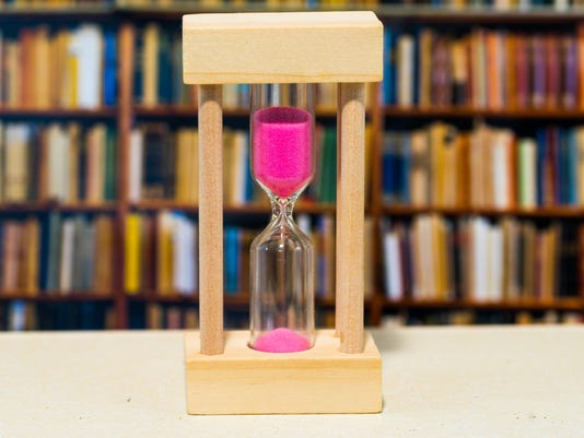 Hourglass against bookshelf