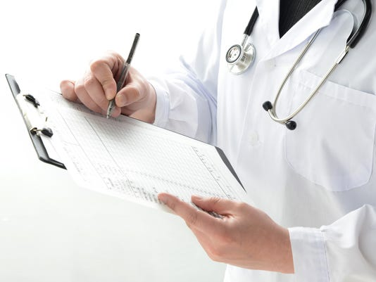 Doctor writing on medical record
