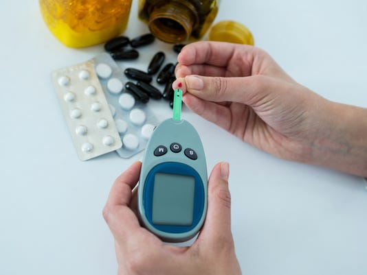 Mans hand testing blood sugar with glucometer