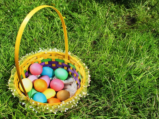 Basket with colorful easter eggs on green lawn