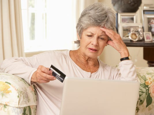 Frustrated Senior Woman Sitting At Home Using Laptop