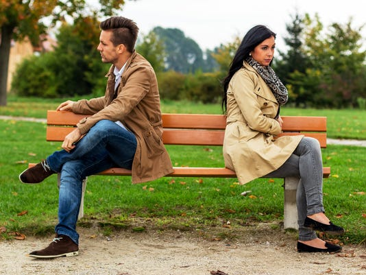 Couple arguing and turned backs sitting on bench