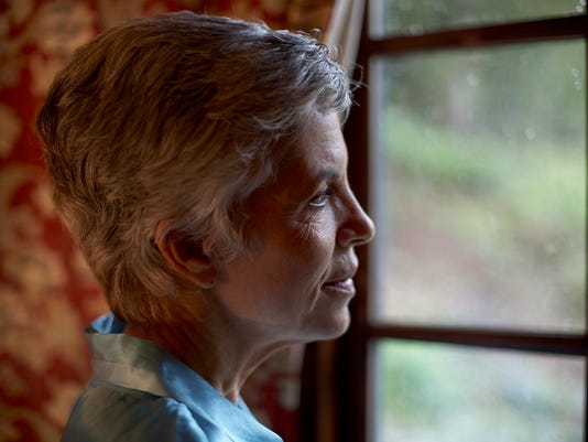 Senior woman looking out window, profile, close-up