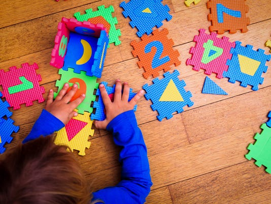little girl playing with puzzle, early education