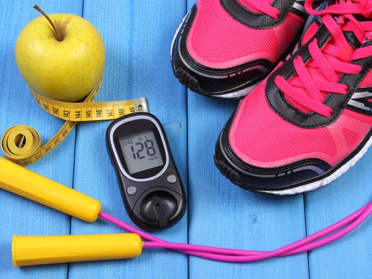 Glucometer, sport shoes, fresh apple and accessories for fitness