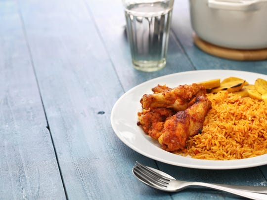 Jollof rice is a favorite in Ghana. Here it is shown with chicken and fried plantain.