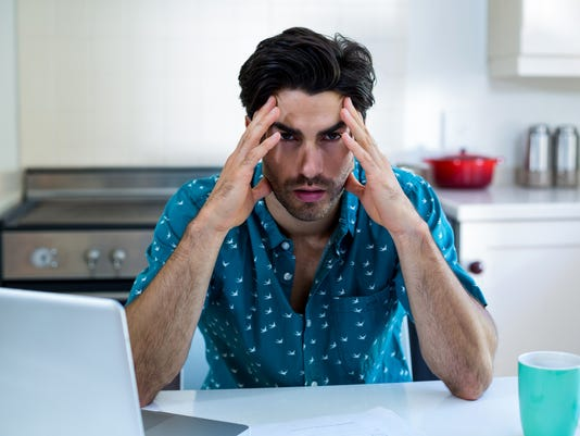 Tensed man sitting with bills and laptop in kitchen