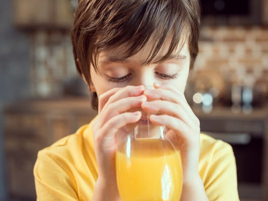 Close-up view of cute little boy drinking fresh orange juice