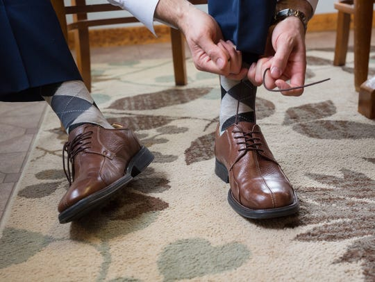 Groom tying his shoes to get ready for his wedding