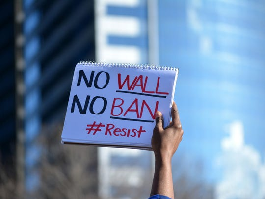 Protester carrying a sign during a march against President Trump's proposed travel ban.
