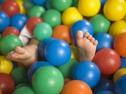 Close-up of a child's feet in a ball pool