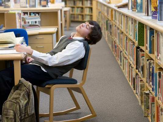 School boy (16-17) sleeping at desk in library