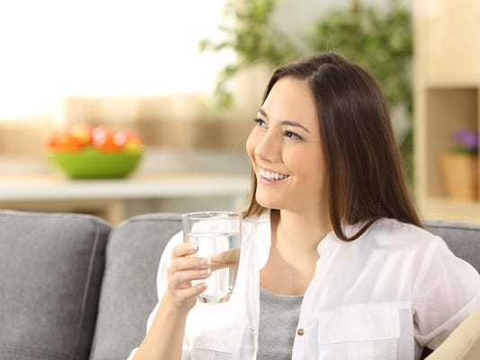 Woman thinking and holding a glass of water