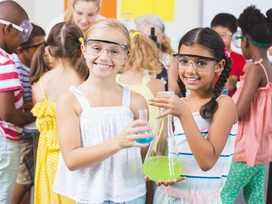 Portrait of kids holding laboratory flask in laboratory