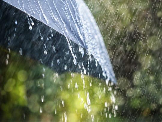 Rain drops falling from a black umbrella.