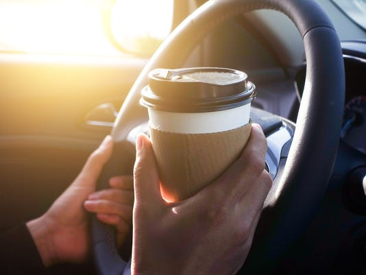 Man holding coffee in car