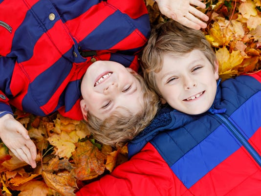 Two little kid boys lying in autumn leaves in colorful fashion fall clothing.