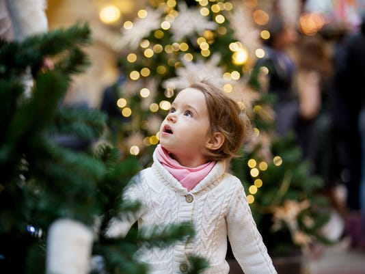 Cute little girl looking at the christmas trees