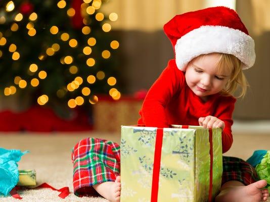 Adorable little girl opening christmas gift