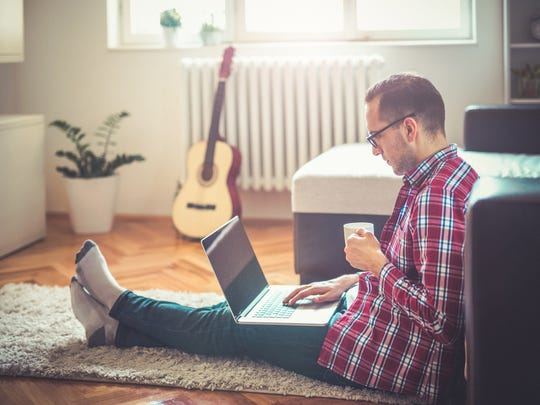 Man sitting on the floor drinking coffee and surfing the internet.