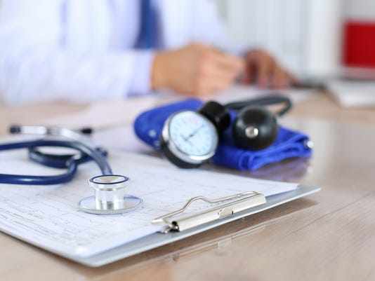 Medical stethoscope lying on cardiogram chart closeup