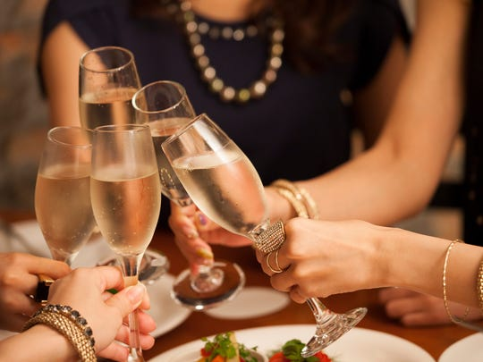 A group toasts with Champagne at a holiday party.