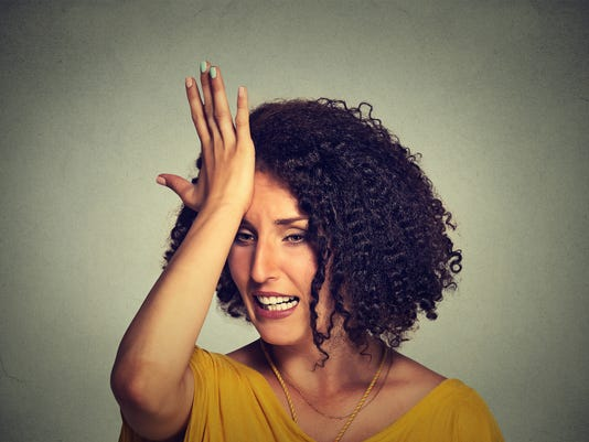 woman slapping hand on head to say duh made mistake