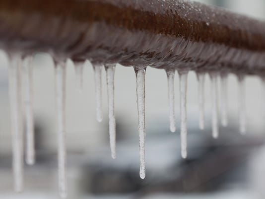 Icicles hanging from a brown pipe. Frozen water and metal surface, winter time concept. selective focus shallow depth of field