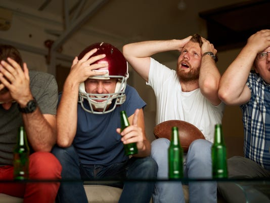 Four friends watching american football game on television, feeling frustrated