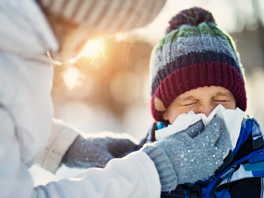Mother blowing nose of her sick son during winter walk