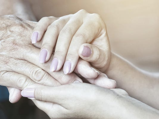 a daughter holding her father's hand on Father's Day