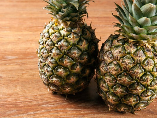 Two pineapples on a wooden background closeup