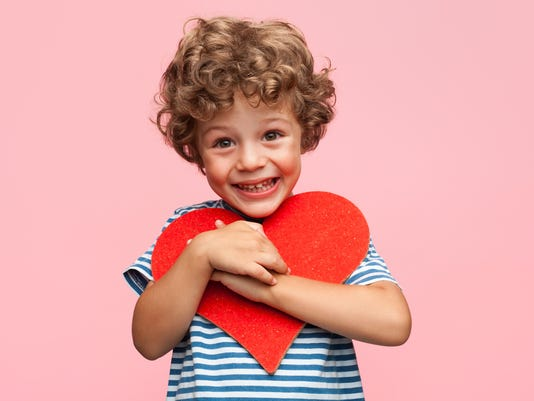 Charming boy posing with heart