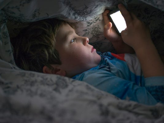 Young boy on cell phone under duvet