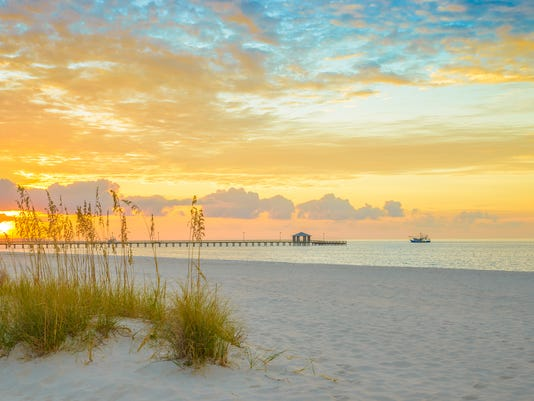 Gulfport Mississippi beach, dramtic golden sunrise, pier, shrimp boat, bay