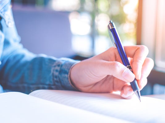Woman hands with pen writing on notebook in the office.