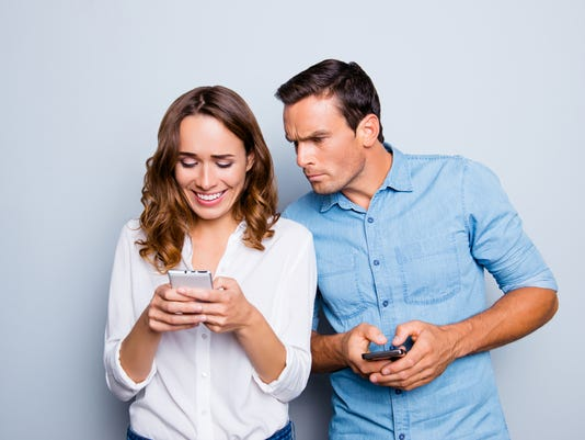 Portrait of lovely couple with smart phones in hands, cheerful charming woman checking her email, man follows her secret correspondence with jealous expression over grey background