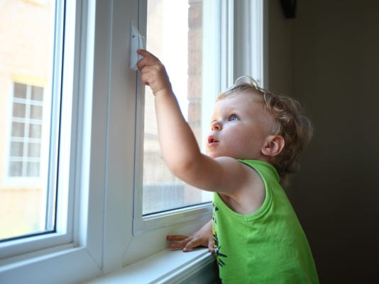 Little boy trying to open the window