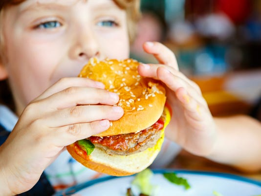 Cute healthy preschool boy eats hamburger sitting in cafe outdoo