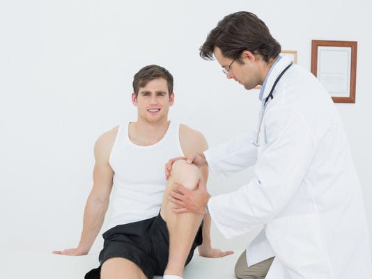 Portrait of a smiling young man getting his knee examined