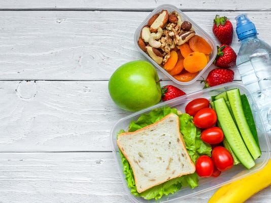 school lunch boxes with sandwich and fresh vegetables, bottle of water, nuts and fruits
