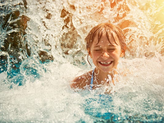 Little girl playing in waterfall in waterpark swimming pool