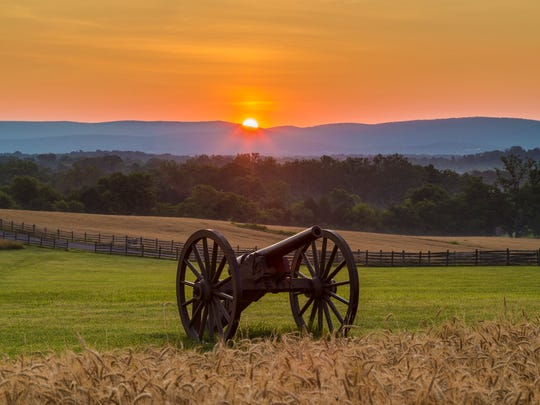 This is a view of the sun rising behind artillery at