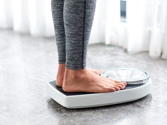 A girl standing on home scales.