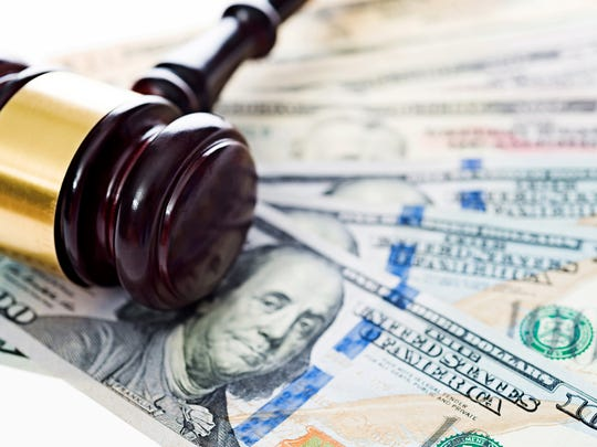 Gavel laying on top of us money.