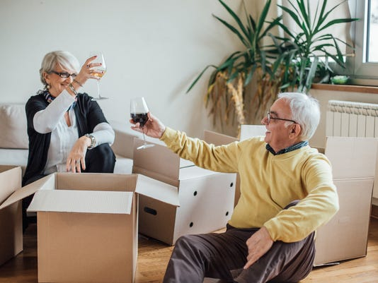 Elderly couple drinking wine at new apartment