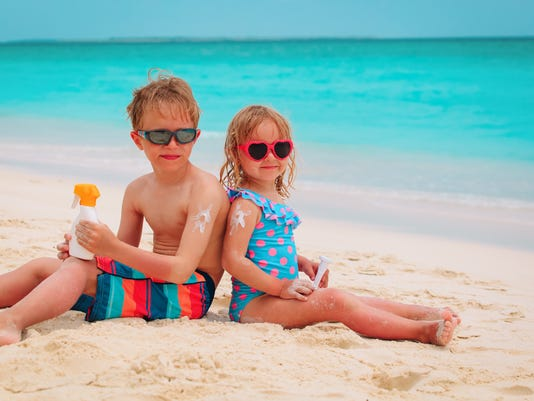 sun protection- happy little boy and girl with suncream at beach